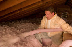 Blow-in fiberglass insulation is installed